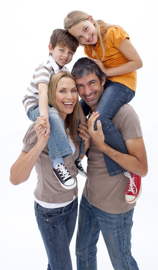 dzieci ojciec daje matki piggyback przejażdżce obraz stock
