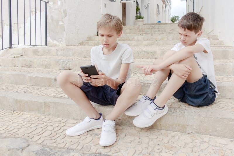 Dzieci opowiada telefon komórkowego outdoors i używa zdjęcia stock