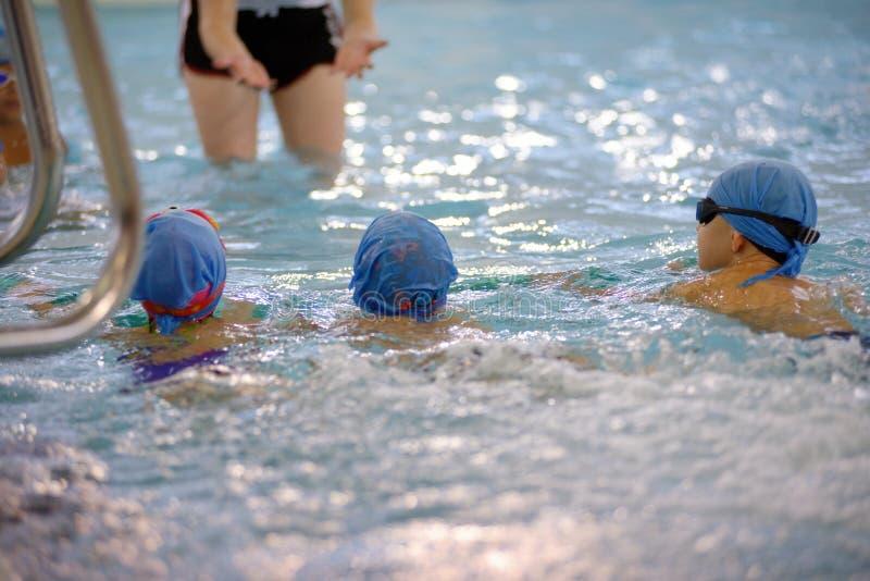Dzieci pływa rywalizację w basenie, sztafetowa rasa zdjęcia royalty free