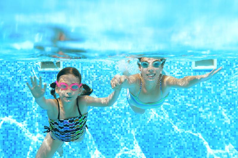 Dzieci pływają w pływackim basenie podwodnym, szczęśliwe aktywne dziewczyny zabawę pod wodą, dzieciak sprawnością fizyczną i spor zdjęcie royalty free