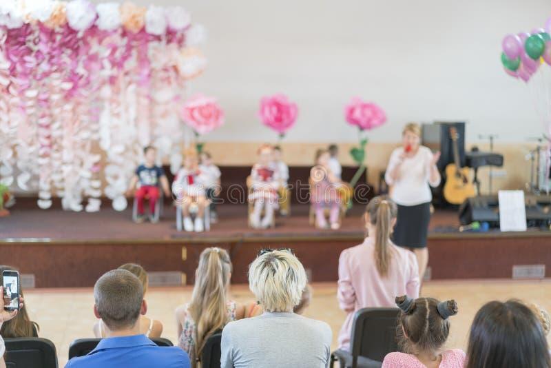 Dzieci partyjni w szkole podstawowej Młode dzieci na scenie w dziecinu pojawiać się w frontowych rodzicach rozmyty fotografia stock