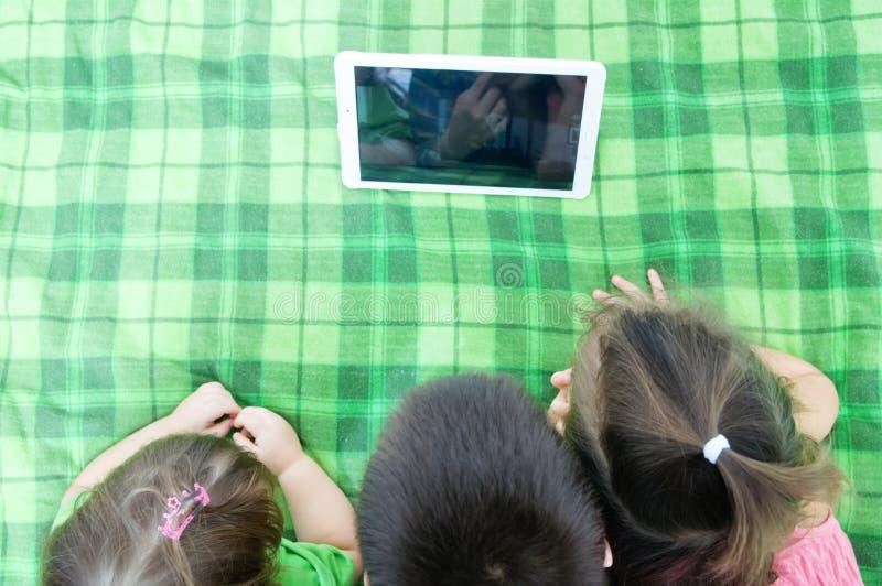 Dzieci patrzeje na ochraniacza lying on the beach na łóżku w domu Dziecko czasu wydatki Trzy dzieciaka używa pastylkę obrazy stock