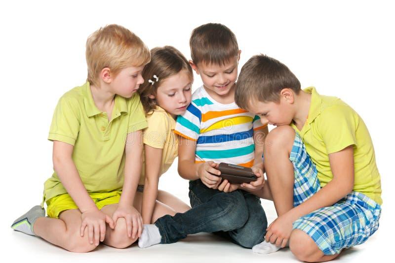 Dzieci plaing z nowym gadżetem fotografia stock