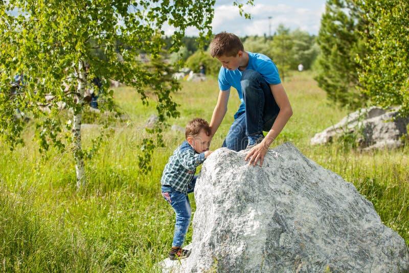 Dzieci pomagają each inny wspinać się skałę zdjęcia royalty free
