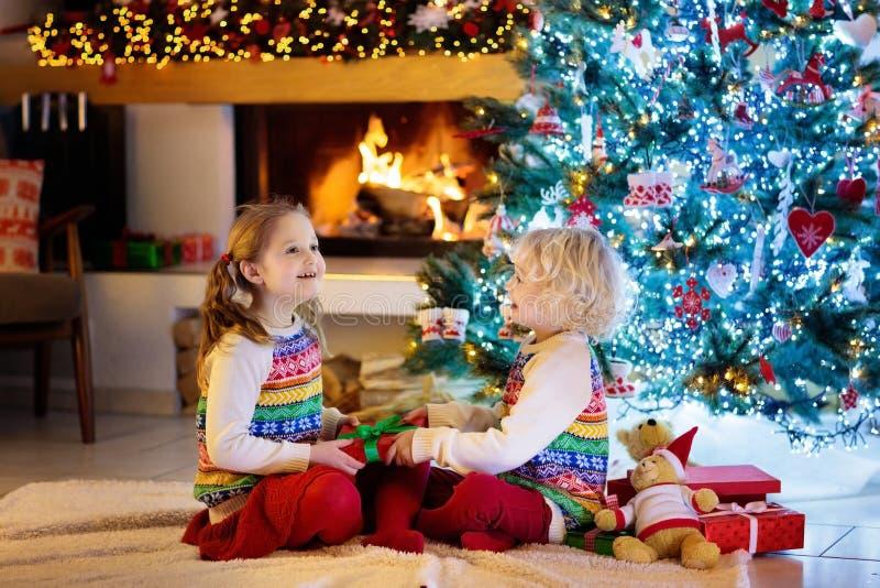 Dzieci przy choinką i grabą na Xmas wigilii Rodzina z dzieciakami świętuje boże narodzenia w domu  obraz stock