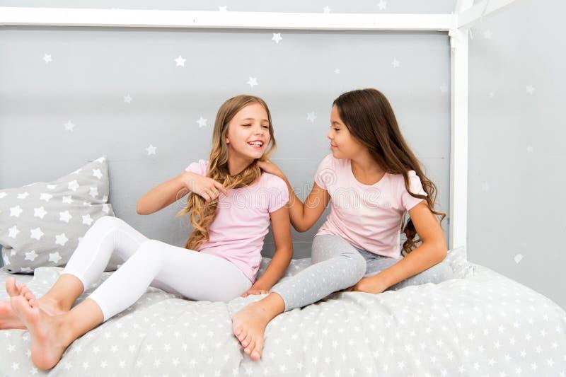 Dzieci relaksują i mieć zabawę w wieczór Siostra czas wolny Dziewczyny w ślicznych piżamach wydają czas wpólnie w sypialni siostr zdjęcia stock