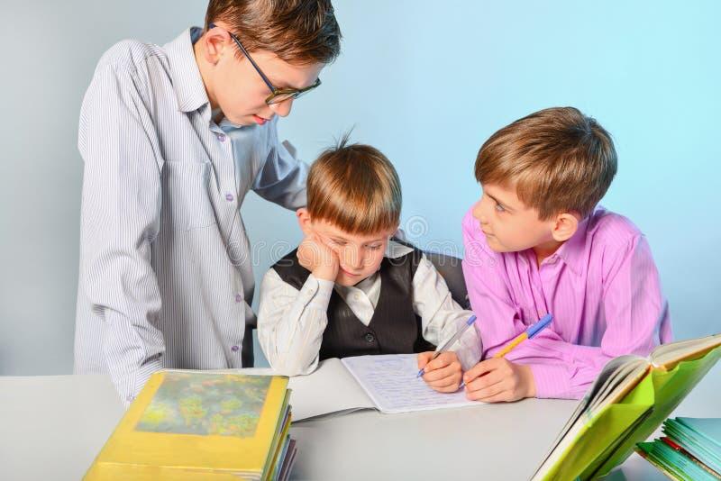 Dzieci robią ich pracie domowej, rozwiązują problemy i dostają gotowymi dla szkoły, zdjęcie stock