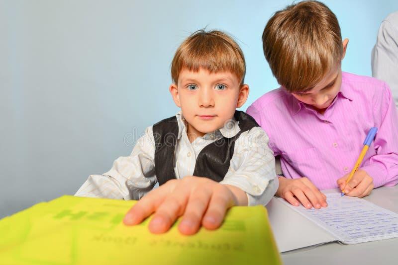 Dzieci robią ich pracie domowej, rozwiązują problemy i dostają gotowymi dla szkoły, obraz stock