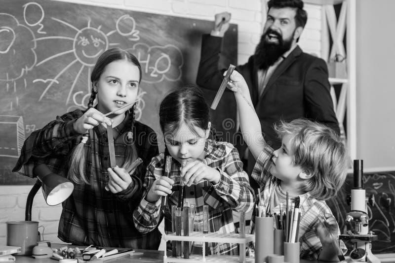 Dzieci robi nauka eksperymentom Edukacja Chemii lab szcz??liwy dziecko nauczyciel tylna szko?y robi? eksperymentom zdjęcia stock