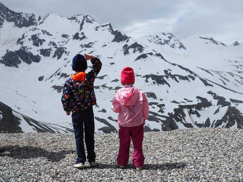 Dzieci rzucają kamienie od falezy z pięknym widokiem nakrywać góry, tylni widok Rosja, czerwiec fotografia stock