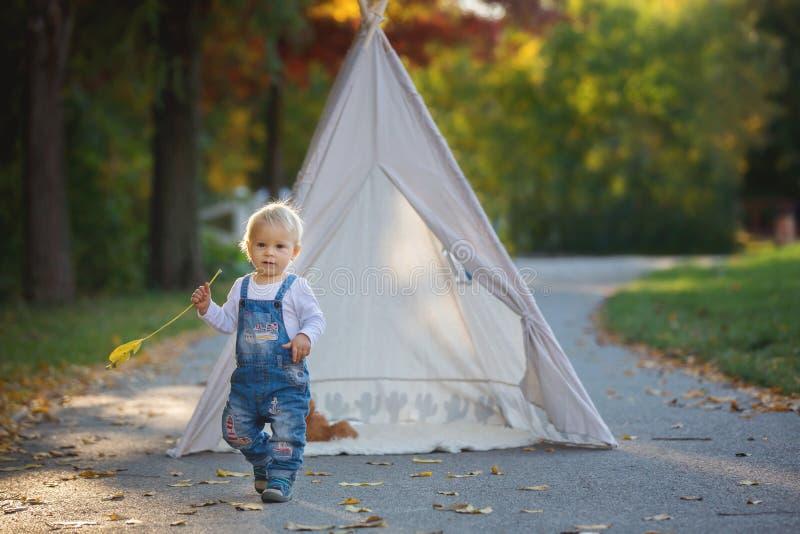 Dzieci, siedzący w namiotowym teepee, trzyma miś zabawkę z obrazy royalty free