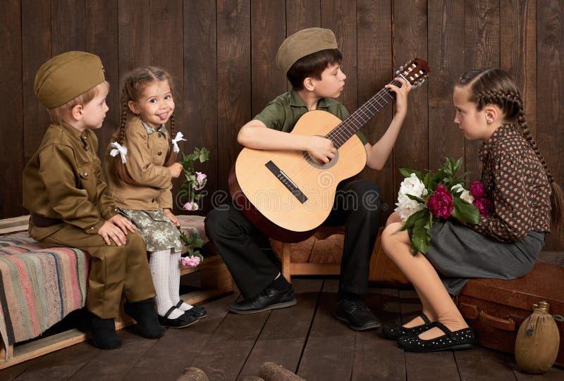 Dzieci siedzi gitarę i bawić się ubierają w retro wojskowych uniformach, wysyła żołnierza wojsko, ciemny drewniany tło, r zdjęcia royalty free