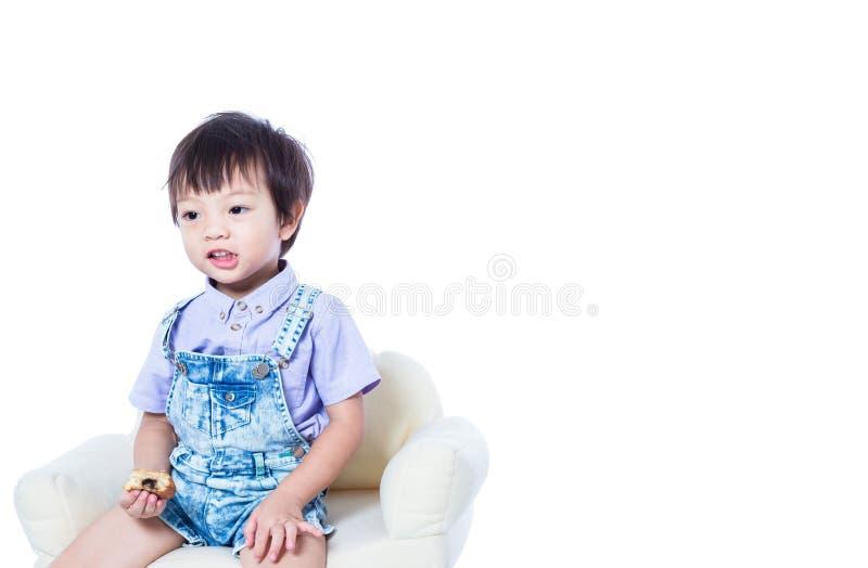 Dzieci siedzi na krześle i trzyma jedzenie fotografia stock