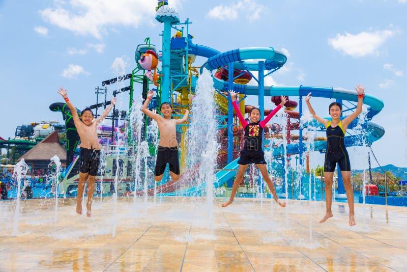 Dzieci skaczą up szczęśliwie przy wodną fontanną przy Cartoon Network obraz royalty free