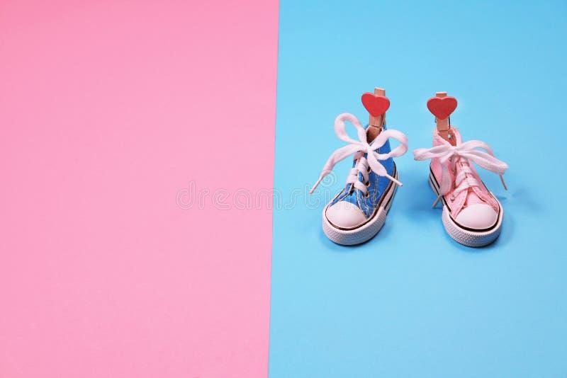 Dzieci sneakers na różowym i błękitnym tle, dziecko prysznic pojęcie zdjęcia stock