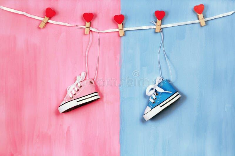 Dzieci sneakers na różowym i błękitnym tle, dziecko prysznic pojęcie fotografia stock