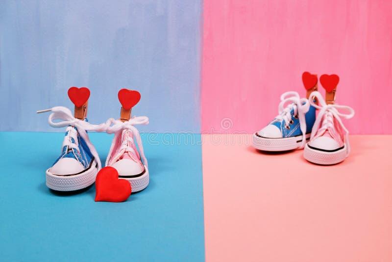 Dzieci sneakers na różowym i błękitnym tle, dziecko prysznic pojęcie obraz stock