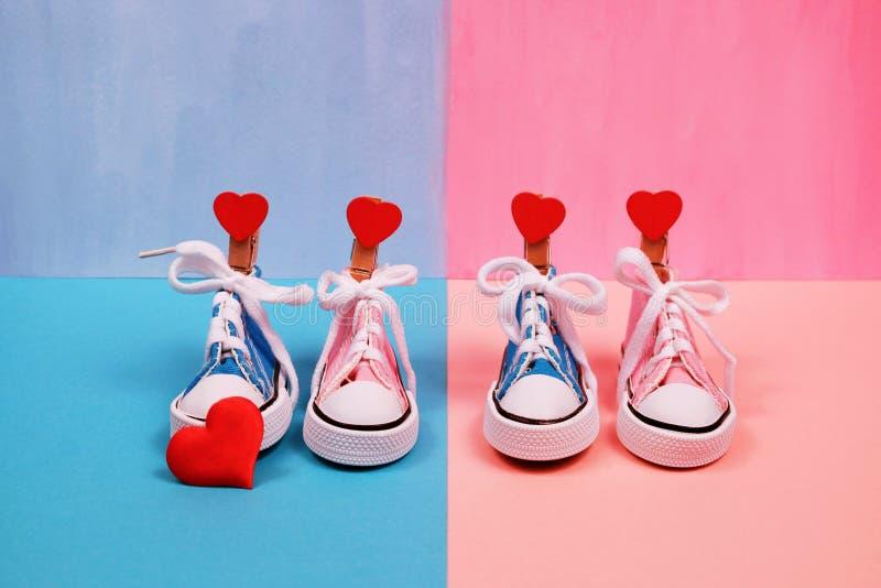 Dzieci sneakers na różowym i błękitnym tle, dziecko prysznic pojęcie obrazy stock