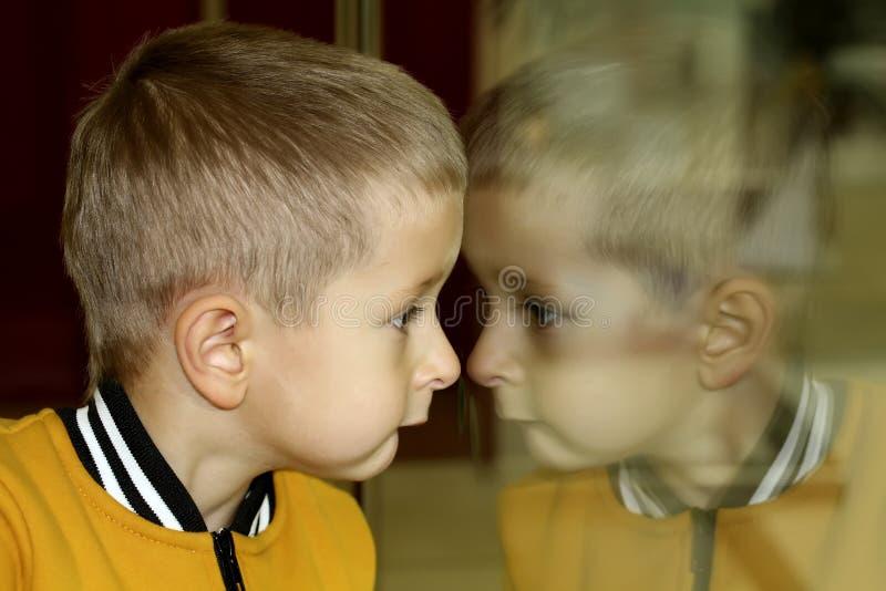 Dzieci spojrzenia w sklep przez szkła szklany odbicie zdjęcia stock