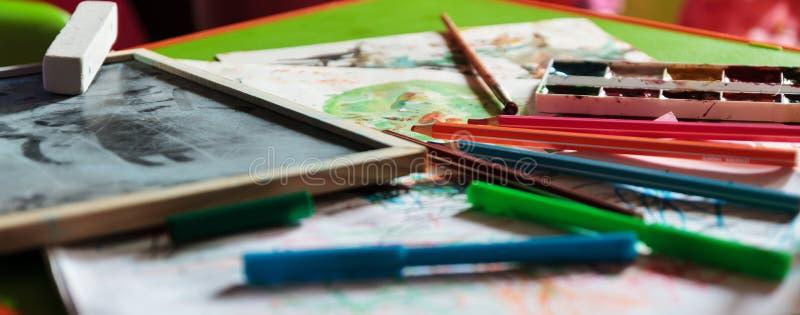 Dzieci stołowi z farbami, białą księgą i kredą dla rysować, zdjęcia stock