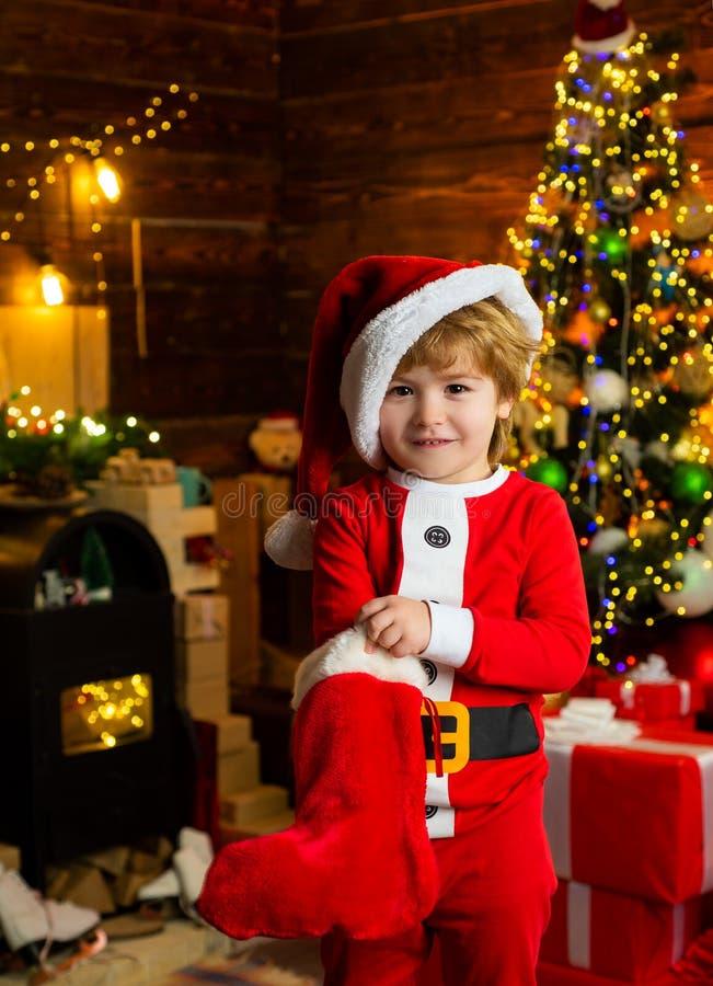 Dzieci?stwo momenty Dzieciak ch?opiec Santa chwyta bo?ych narodze? prezent Bo?enarodzeniowy po?czochy poj?cie Dziecko rozochocona obrazy stock