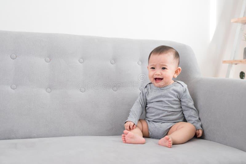 Dzieci?stwo, niemowl?ctwo i ludzie poj??, - szcz??liwy ma?y dziewczynki obsiadanie na kanapie w domu zdjęcia stock