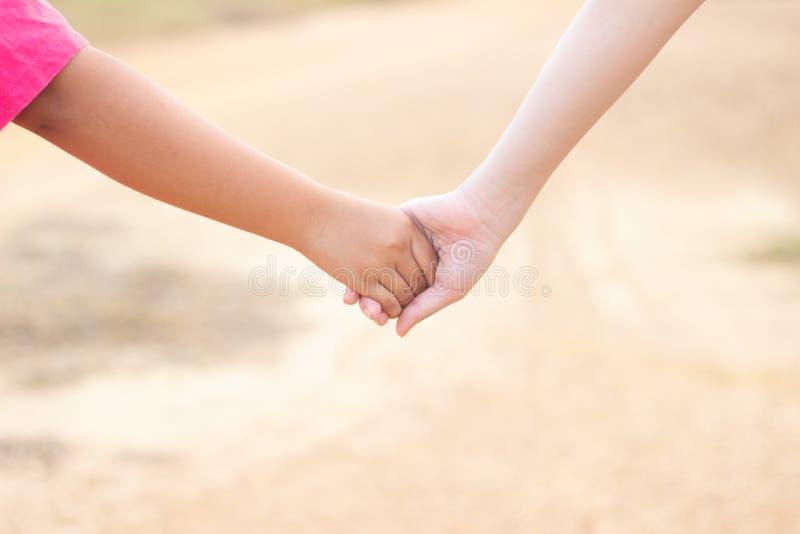 Dzieci trząść ręki z plamy tłem, przyjaźń, dziewczyna chwyta one& x27; s ręki chodzi w drogowym plamy tle zdjęcia royalty free