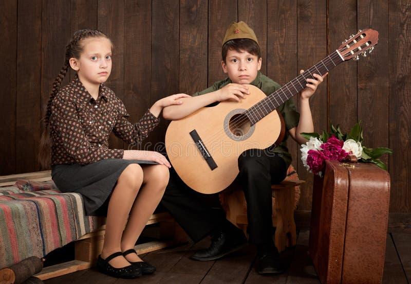 Dzieci ubierają w retro wojskowych uniformach wysyła żołnierza wojsko, ciemny drewniany tło, retro styl zdjęcie stock
