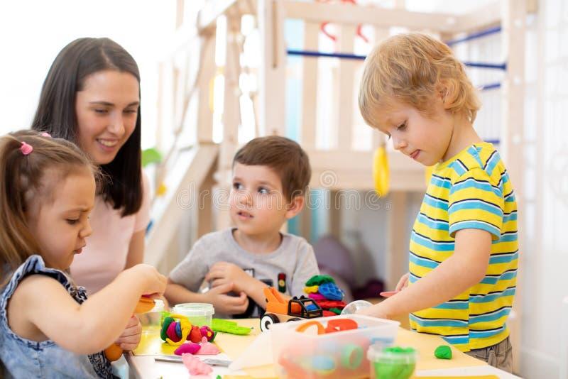Dzieci uczy się pracować kolorowego sztuki ciasto w pepiniery, dziecina lub opieki dziennej centrum, zdjęcia stock