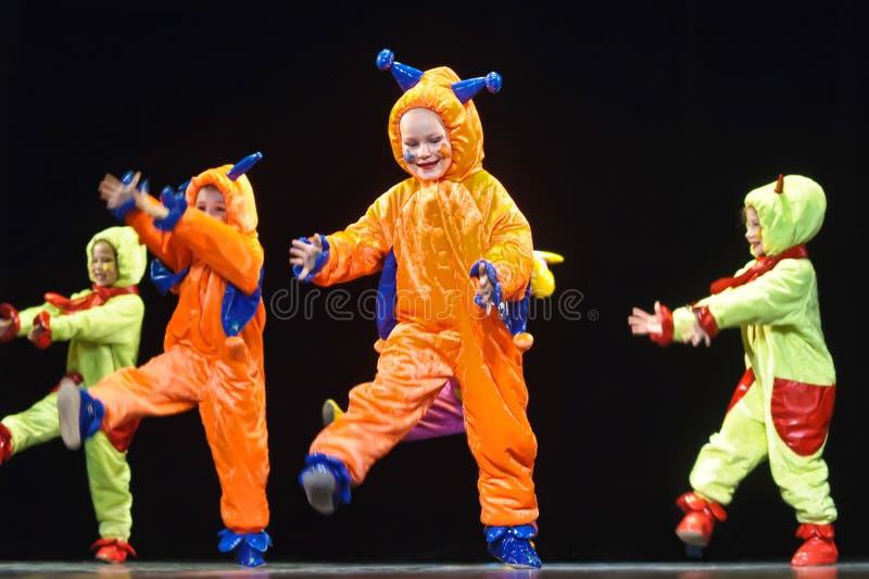 Dzieci w śmiesznych barwionych kombinezonów obcych tanczy na scenie zdjęcie stock