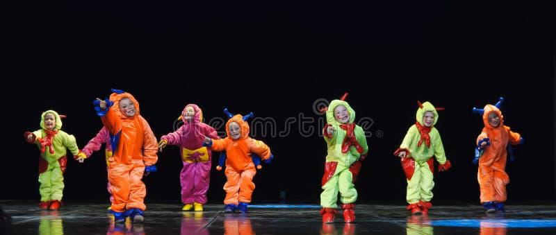 Dzieci w śmiesznych barwionych kombinezonów obcych tanczy na scenie obraz stock