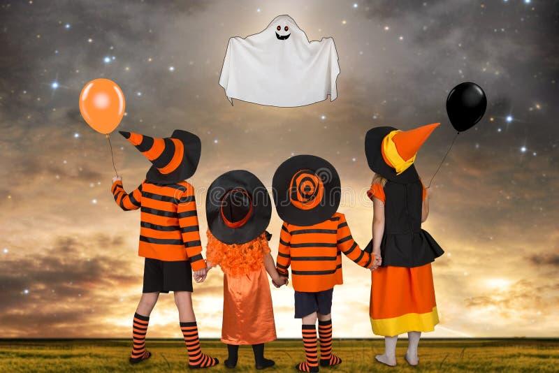 Dzieci w Halloweenowym kostiumu spojrzeniu przy latającym duchem fotografia stock