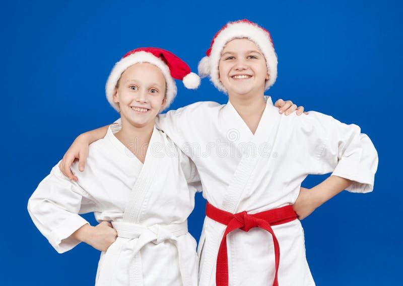 Dzieci w karategi i nakrętki Święty Mikołaj stoją z uśmiechem obraz royalty free