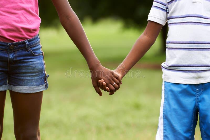 Dzieci w miłości czernią chłopiec i dziewczyny mienia ręki obraz stock