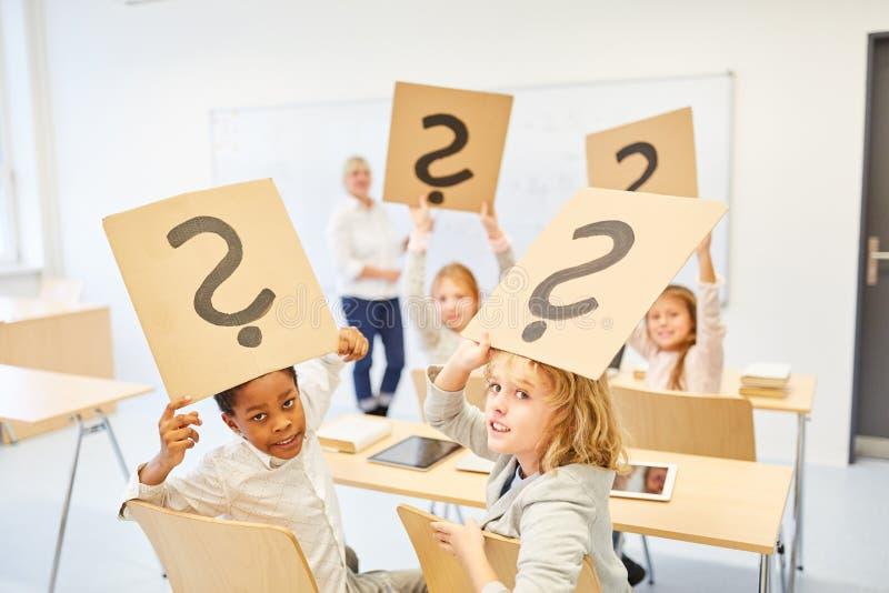 Dzieci w szkoły podstawowej utrzymania znak zapytania fotografia stock