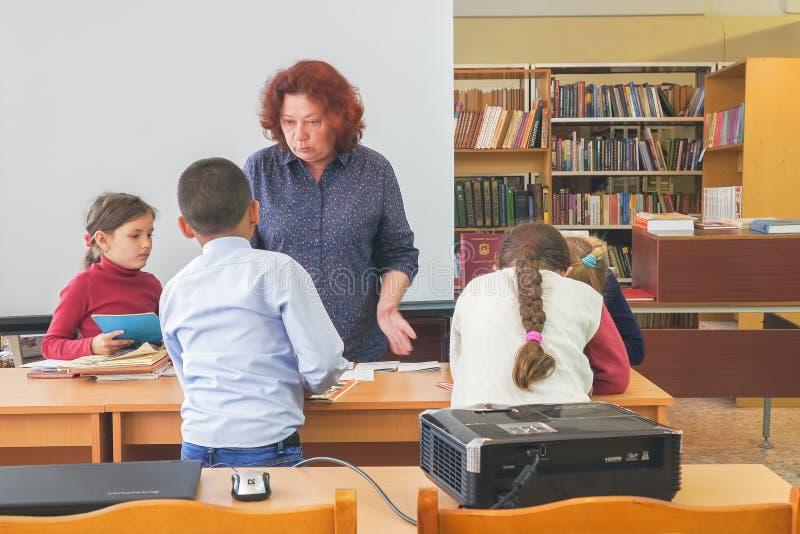 Dzieci w wieku szkolnym stoj? obok nauczyciela biurka obraz royalty free