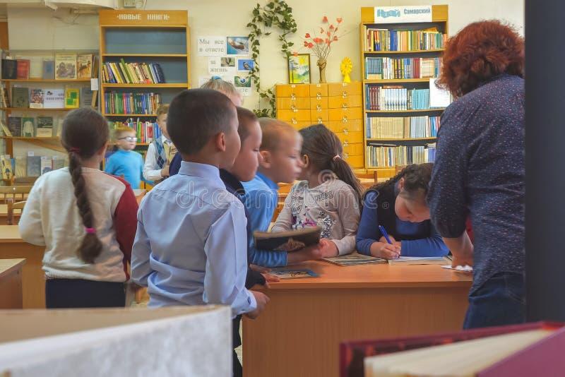 Dzieci w wieku szkolnym stoj? obok nauczyciela biurka obraz stock