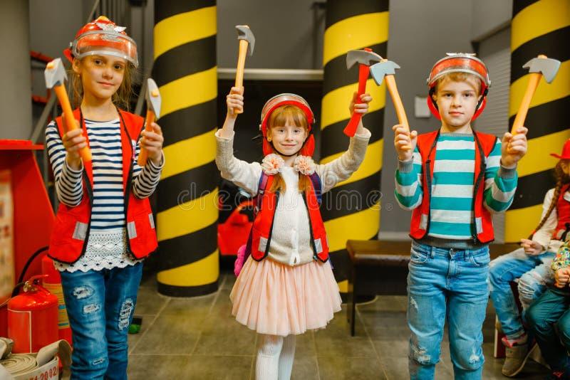 Dzieci z narzędziami w rękach bawić się strażaków zdjęcie royalty free
