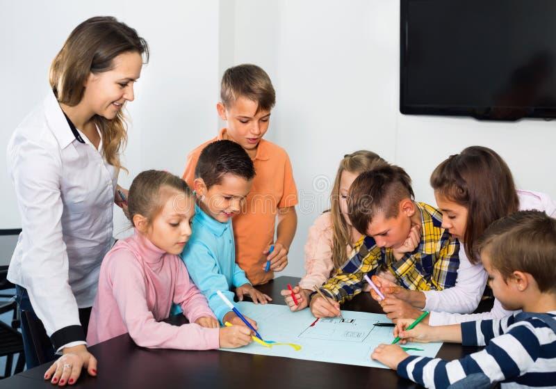 Dzieci z nauczycielem rysunkowym w sala lekcyjnej wpólnie obrazy stock