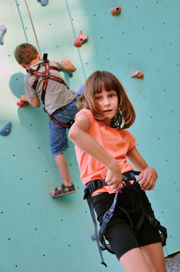 Dzieci z wspinaczkowym wyposażeniem przeciw szkolenie ścianie zdjęcie royalty free