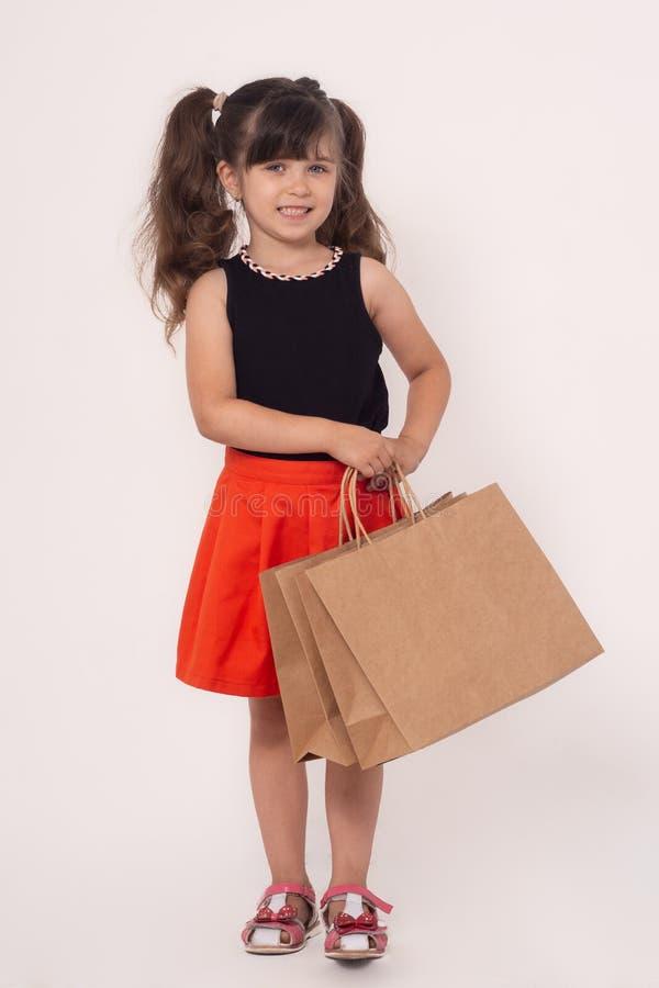 Dzieci z zakupami odizolowywającymi na białym tle Dzieciak z torba na zakupy zdjęcie stock