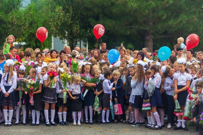 Dzieci zapisywali się w pierwszej klasie z bukietami kwiaty i balony w rękach, nauczycielach i szkoła średnia uczniach na, fotografia stock