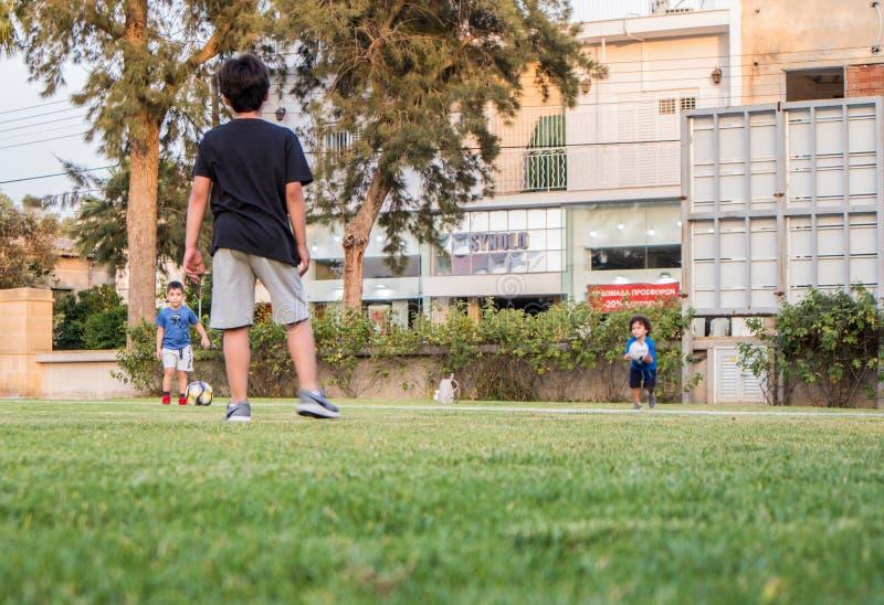 Dzieciaków bawić się footbal na zielonej trawie w domu ogródzie, obrazy royalty free