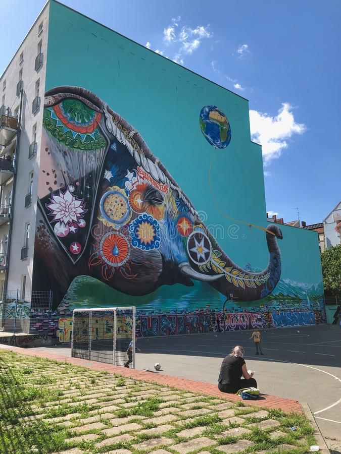 Dzieciaków bawić się plenerowy na piłki nożnej boisku na ulicie z graffiti malowidłem ściennym w tle w Berlin, Kreuzberg obraz royalty free