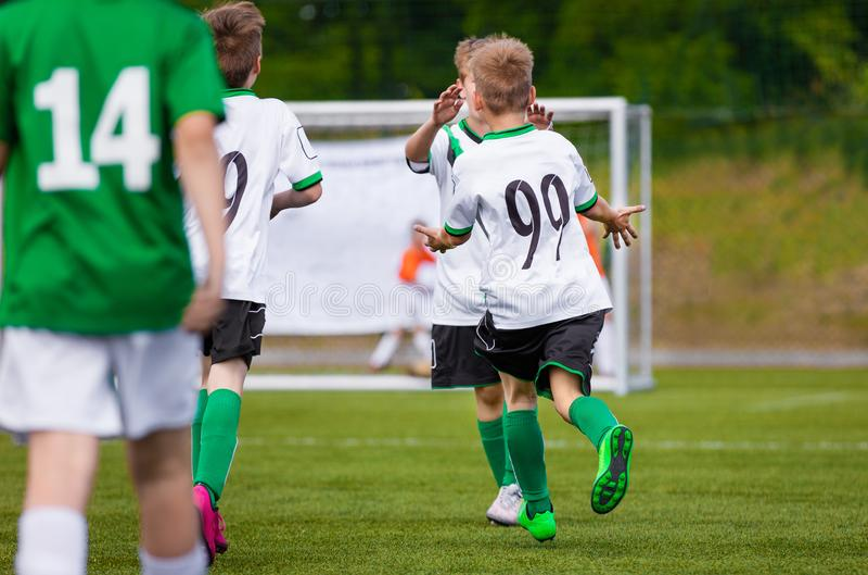 Dzieciaków graczów piłki nożnej celu świętowanie Szczęśliwi dzieci Bawić się Futbolowego dopasowanie fotografia stock