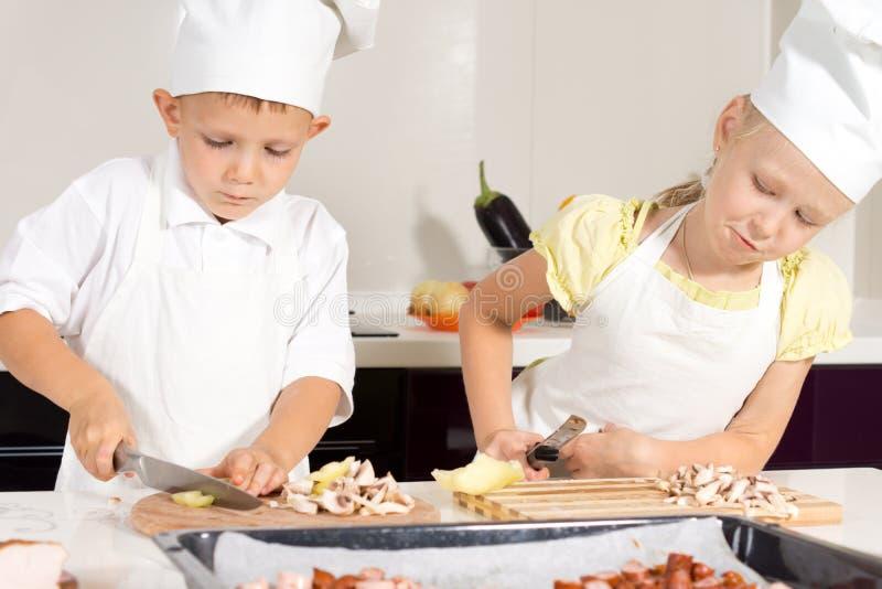 Dzieciaków szefowie kuchni Pokrajać składniki na ciapanie desce obrazy royalty free