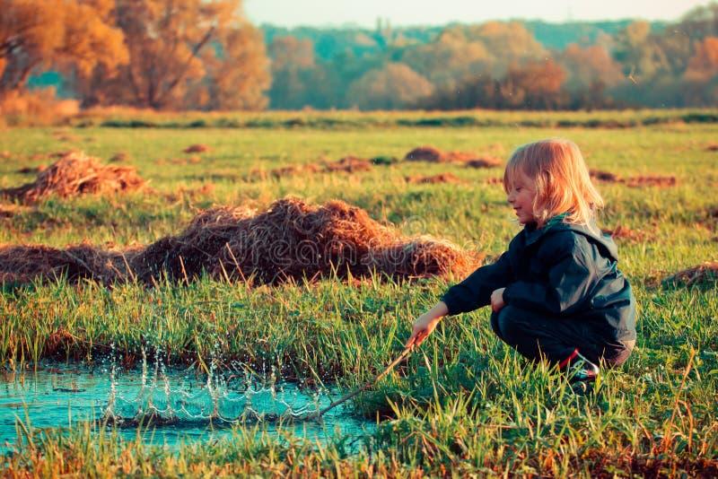Dzieciak bawić się w kałuży zdjęcia stock