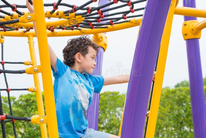 Dzieciak chłopiec ma zabawę bawić się na dziecka ` s pięcia zabawce przy szkołą zdjęcie stock