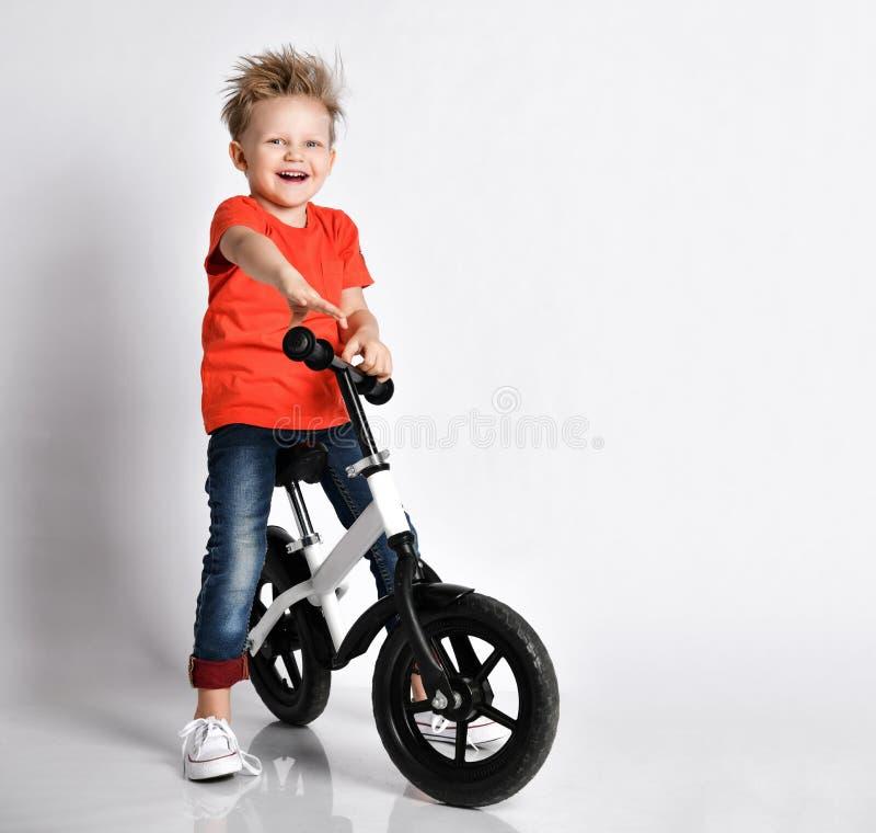 Dzieciak chłopiec w pomarańczowej koszulce i niebiescy dżinsy rowerzyście szczęśliwych jechać nowego chłodno bicykl obraz stock