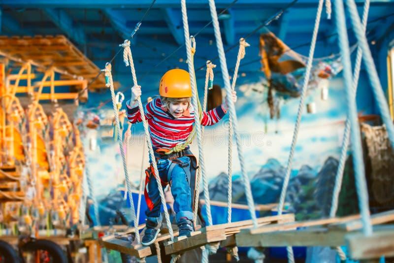 Dzieciak cieszy się bawić się i letniego dzień Szczęśliwy dziecko ma zabawę w przygoda parku, wspinaczkowe arkany zdjęcia royalty free